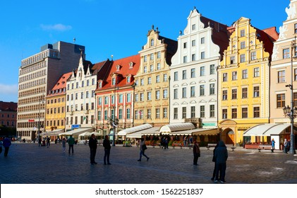 MARKET SQUARE, WROCLAW, POLAND - OCTOBER 6, 2019: Colorful houses of the medieval Wroclaw Market Square and a Santander Bank Polska office on a sunny morning. The square is a major tourist attraction.