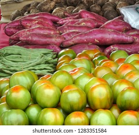 A market stall sells fresh vegetables, such as tomatoes, borad beans and sweet potatoes