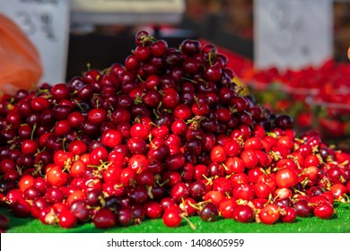 At a market stall at a Spanish weekly market red juicy cherries are sold. They are lying in a big pile. Some are bright red, others are dark.