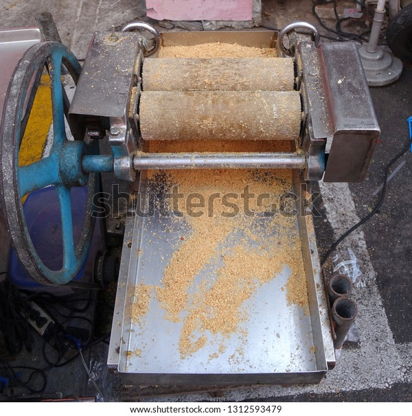 A market stall uses a hand-operated vintage peanut crusher to make peanut candy