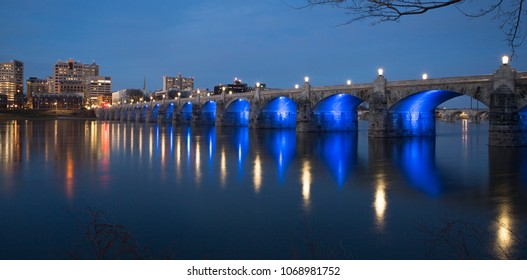 Market Street Bridge in Harrisburg PA at dusk with blue lights under the bridge reflecting on the river