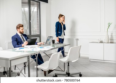 Marketer or analityc manager team dressed in suits working with paper charts and laptops at the white office interior