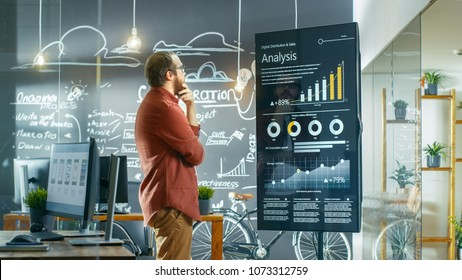 Marketer Looks at Interactive Touchscreen Whiteboard Showing Latest Graphs and Charts on Statistical Growth. He Works in the Creative Office.