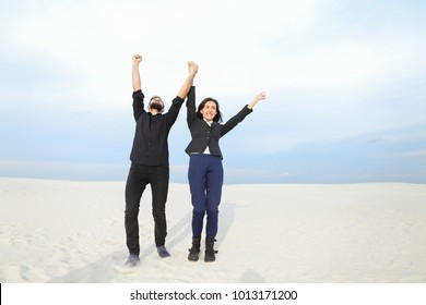 Marketers male and female stop by seaside after last working day before vacation, young people rejoicing at beginning of rest. Bearded guy and fair-haired girl dancing among sands. Concept o