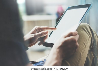 Marketing brand manager reading business news modern Interior Design Loft Office.Man relax Vintage Sofa,Use contemporary tablet,share information.Blurred Background.New Startup Idea.Process Closeup