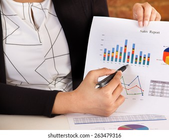 Marketing executive making a business presentation and analyzing sales report with charts and graphs