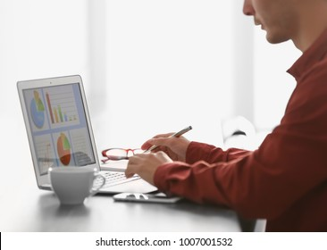 Marketing manager using laptop at table in office