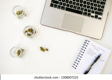 Marketing for Marijuana Business on White Table Work Space with Glass Jars of Cannabis