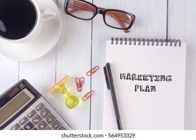 MARKETING PLAN text on notebook.coffee,calculator,pen,rubber stamp,glasses on the desk.top view.