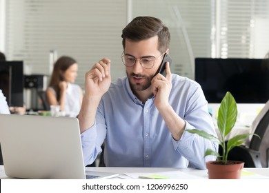 Marketing sales manager consulting client making offer selling talking on phone near laptop in office, serious business man making call negotiating speaking by mobile holding interview on cellphone