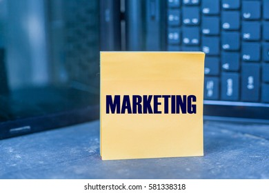 MARKETING word on blank note on wooden table over blurry laptop as a background