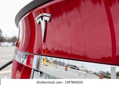 MARKHAM, CANADA - April 24, 2019: Red Tesla Model S rear badge and text as vehicle is supercharged at Tesla CF Markham Supercharger.