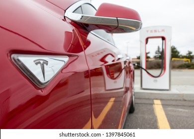 MARKHAM, CANADA - April 24, 2019: Red Tesla Model S side-view as vehicle is supercharged at Tesla CF Markham Supercharger.