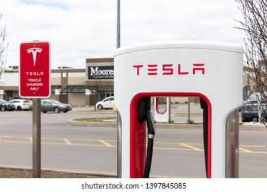 "MARKHAM, CANADA - April 24, 2019: Tesla Supercharger and Tesla ""Electric Vehicle Only"" Sign at SmartCentres Markham Woodside."
