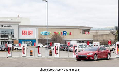 MARKHAM, CANADA - April 24, 2019: Red Tesla Model S supercharging at the Tesla Supercharger in-front CF Markham Shopping Centre.