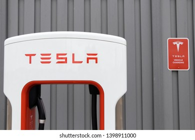 MARKHAM, CANADA - April 24, 2019: Tesla Supercharger and Tesla Electric Vehicle Only Sign against grey fence at CF Markvile, Markham Shopping Centre.