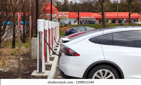 MARKHAM, CANADA - April 24, 2019: White Tesla Model X, Red and Blue Tesla Model all plugged in, supercharging at SmartCentres Markham Woodside, Tesla Supercharger.