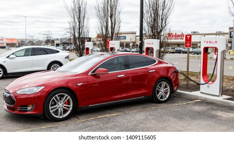 MARKHAM, ONTARIO - APRIL 24, 2019: Red Tesla Model S and White Tesla Model X plugged-in, and supercharging.