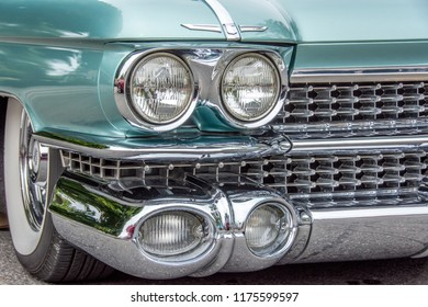 Markham, Ontario / Canada – September 9, 2018: The front quarter panel, headlight housings, and chrome grill and bumper, and white wall tire of a vintage classic green 1959 Cadillac Eldorado.