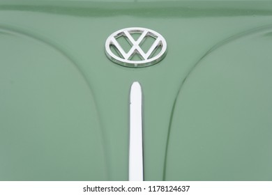 Markham, Ontario / Canada – September 9, 2018: A closeup of the shiny chrome hood ornaments on a vintage classic green Volkswagon beetle.
