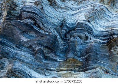 Marks of sea water and wind erosion on a blue-toned, from light to dark, rock.The natural process of erosion created smooth and fluid lines, holes and layers. It looks like it was carved.