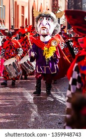 Marktplatz, Basel, Switzerland - March 13th, 2019. A drum major in purple red costume leading his group in the street