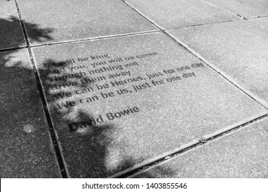 Marlborough, New Zealand - Jan 2019: Inspirational quote of 'Heroes' song lyrics by David Bowie on pavement floor, in stone.