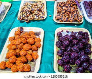 Marmalade balls, sprinkled with dried berries and sweet sawdust. Balls with nuts and marmalade. Trays with Indian sweets. Kozinaki and marmalade.