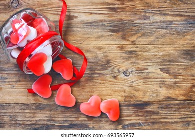Marmalade candy shape heart in glass jar with ribbon, gift for Valentine's Day, top view, space for text