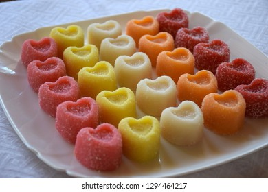 Marmalade heart-shaped candies. Colorful bright marmalade sweets on white plate on a White Background. Heart candies coated with sugar. Candy Valentines Hearts.