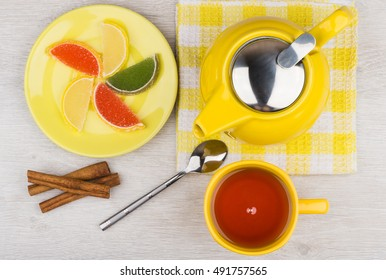 Marmalade, hot tea and teapot, cinnamon sticks on wooden table. Top view
