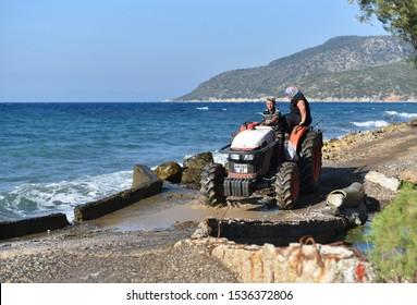 Marmaris / Turkey - 10.08.19: Couple farmers comeback from plantation on tractor Kubota by seaside road