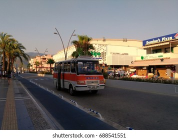 MARMARIS - TURKEY - JULY 2017: Red shuttle bus is moving along the route. Urban transport, street scene