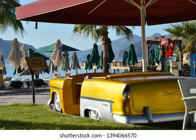 "Marmaris,Turkey.The middle of September 2016.View of seaside restaurant ,, Big yellow taxi""with yellow car in retro style on the background of Marmaris beach."