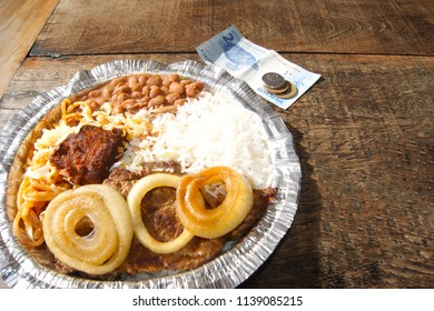 Marmite or marmitex or warm, travel meal next to Brazilian banknotes and coins - real. Economical price.