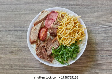 Marmitex with white rice, beans, cabbage, pasta and barbecue with side dish of cabbage, crumbs and gnocchi on a textured wooden table - top view.