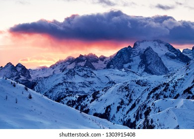 Marmolada mountain peak covered in snow at sunset. Hot red sun. Italy