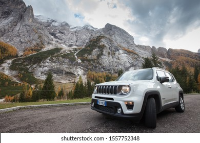 Marmolada, Trentino and Veneto region / Italy - October 2019 : White Jeep Renegade suv at car park at foot of mount Marmolada, the highest peak in Dolomites.