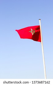Maroccan national flag swings under the blue sky