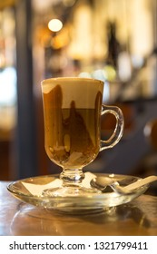 Marocchino coffee served in a small glass with a shot of espresso, cocoa powder and milk froth.