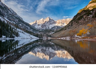 Maroon Bells and Maroon Lake with reflection of rocks and mountains in snow around at autumn in Colorado Rocky Mountains, USA.