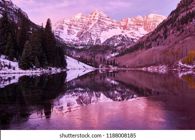 Maroon Bells and Maroon Lake with reflection of rocks and mountains in snow at sunrise around at autumn in Colorado Rocky Mountains, USA.