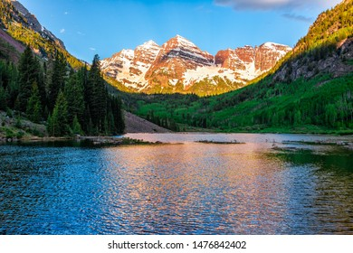 Maroon Bells lake at sunrise in Aspen, Colorado during blue hour dawn with rocky mountain peak and snow in June 2019 summer and vibrant light reflection