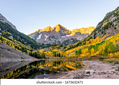 Maroon Bells lake at sunrise sunlight in Aspen, Colorado with rocky mountain peak and snow in October 2019 autumn and vibrant trees reflection on water