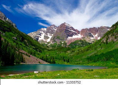 Maroon Bells Mountain Peaks in the summer with Marron Lake in foreground and two hikers on edge of lake