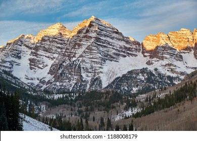 Maroon Bells mountains in snow at sunrise in Colorado Rocky Mountains, USA.