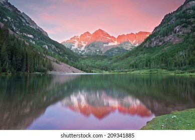 Maroon Bells snow capped peaks reflected in a lake at sunrise