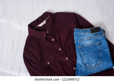 Maroon corduroy shirt and blue jeans on wooden background. Fashion concept