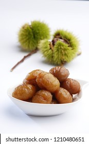 maroon glace in a white plate, fresh chestnuts on background, candied chestnuts, sweet