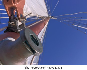 maroon mast and white sail view of sailboat from below under blue sky